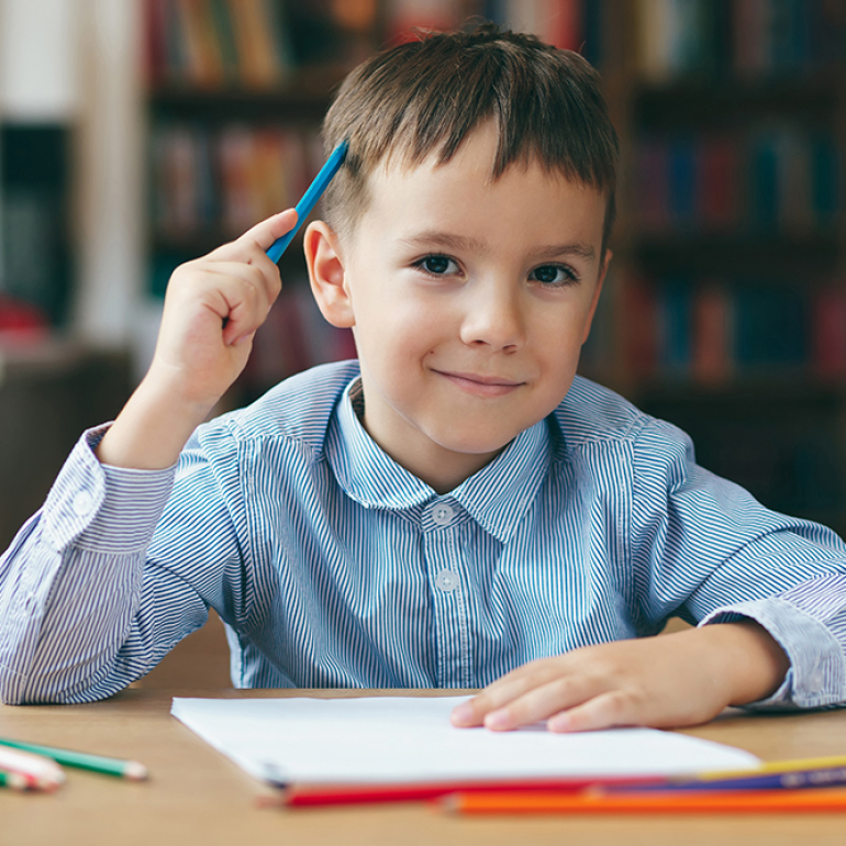 Cute  smiling boy doing homework,  coloring pages, writing and painting . Children paint. Kids draw. Preschooler with books in the library. Colorful pencils and paper on a desk. Creative boy.