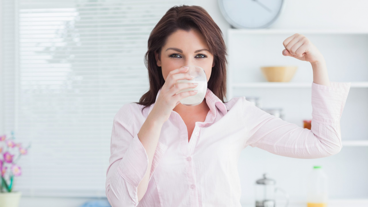 Portrait of young woman drinking milk and flexing muscles in the kitchen