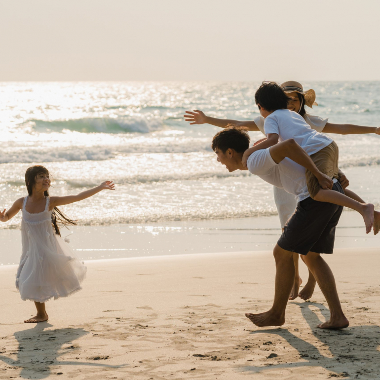Asian young happy family enjoy vacation on beach in the evening. Dad, mom and kid relax playing together near sea when sunset while travel holiday. Lifestyle travel holiday vacation summer concept.
