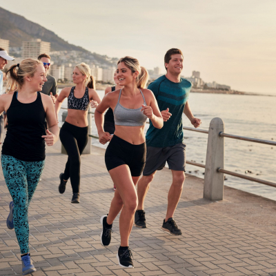 50988703 - portrait of young runners enjoying workout on the sea front path along the shoreline.  running club group running along a seaside promenade.