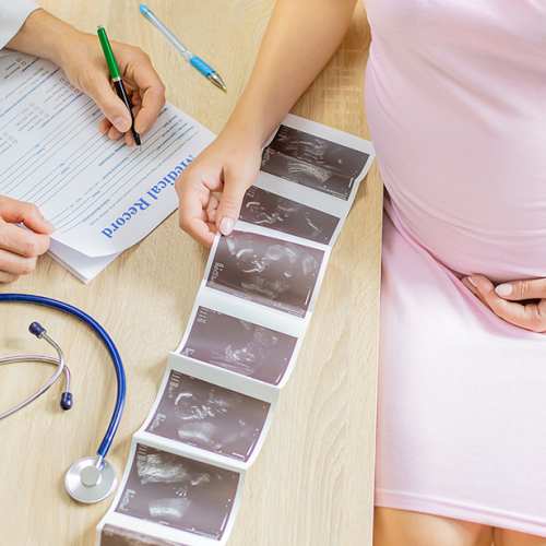 A doctor in a clinic examines a pregnant woman. Selective focus. People.