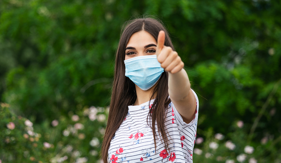 Portrait of young woman wearing face protective mask to prevent Coronavirus and anti-smog. Portrait of young woman wearing face mask. Thumb up