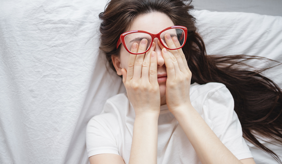 Young woman rubs her eyes after using glasses. Eye pain or fatigue concept, poor vision.